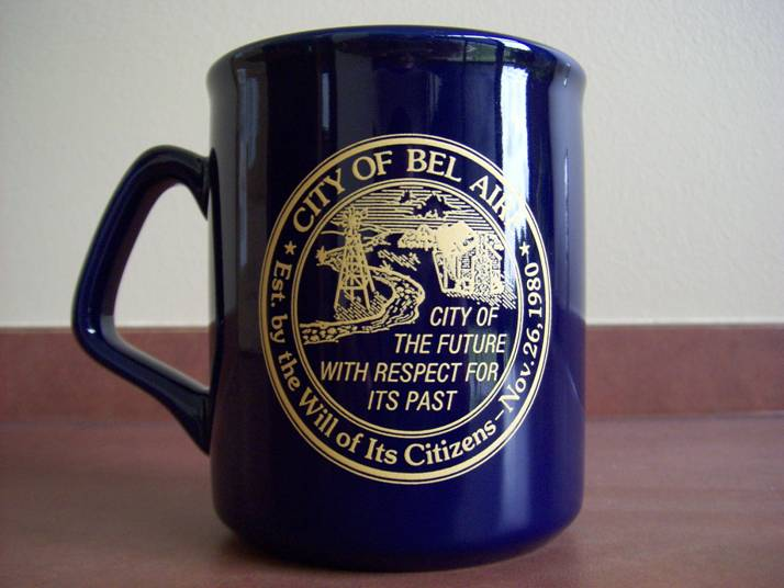 A blue coffee mug with gold print of the Bel Aire logo and motto